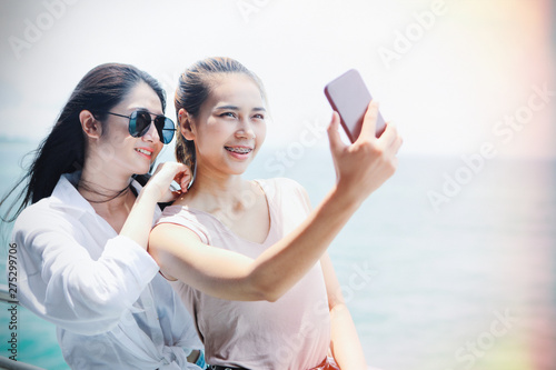 Cuadros en Lienzo Two Asian girls are using smart phones to take self-portraits while traveling