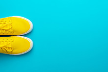 Top View Of Skateboarding Shoes With Copy Space. Pair Of Yellow Sneakers On Turquoise Blue Background. Minimalist Photo Of Yellow Sneakers With Tied Shoelaces. Flat Lay Image Of Yellow Summer Footwear