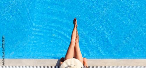 Sexy woman in bikini and sunhat relaxing in swimming pool. Wallpaper Mural