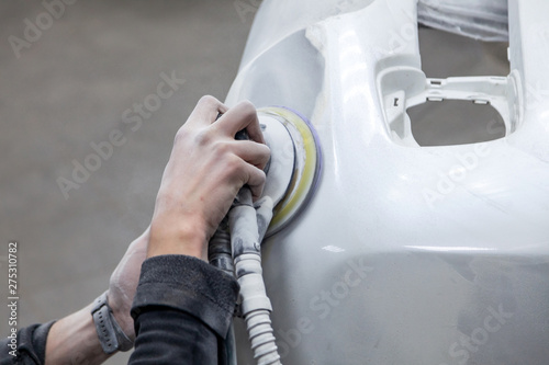 Preparation for painting a car element using sander and putty by a service techn Wallpaper Mural
