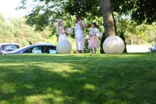 Dziewczynki Z Balonami Na Wzniesieniu Pokrytym Zieloną Trawą.