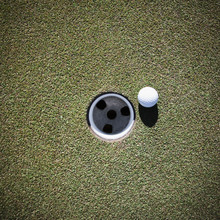Golf Ball Next To A Putting Cup