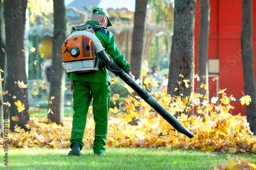 Photo Working in the Park removes autumn leaves with a blower
