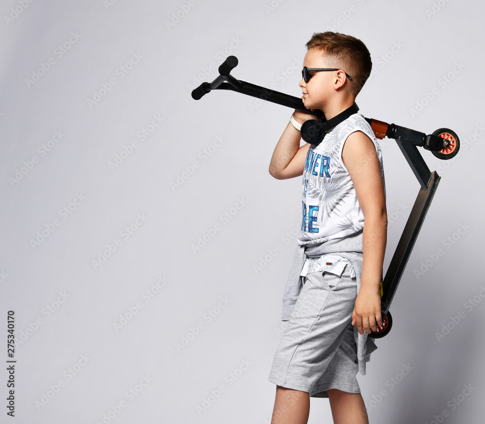 Fototapety, obrazy: teen boy posing in studio with scooter scooter on a light background in summer clothes