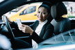 Portrait of cheerful female professional holding cellphone gadget in hand and sitting in car as driver for steering to financial district, happy smiling woman using digital technology for phoning