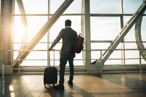 Fototapeta  Businessman at Airport Terminal Boarding Gate Looking Through Window