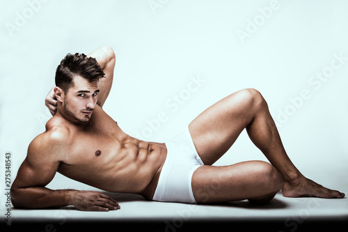 Fotografie, Obraz  Portrait of handsome young man with stylish haircut in white underwear posing over white background