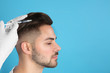 Young man with hair loss problem receiving injection on color background. Space for text