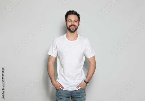 Obraz Young man in t-shirt on light background. Mock up for design - fototapety do salonu