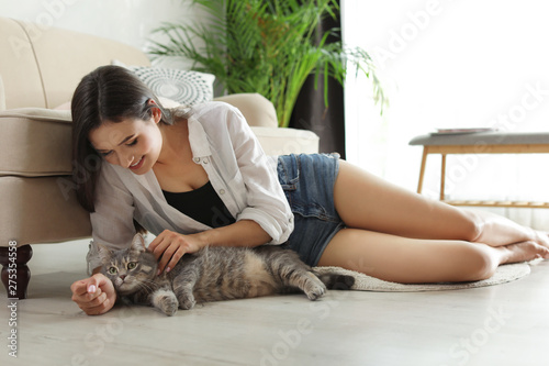 Fotografía  Young woman with cute cat at home. Pet and owner
