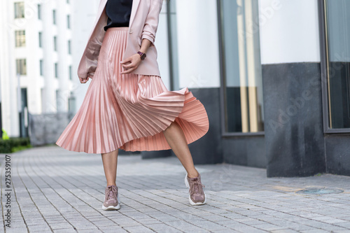Obraz na plátně Pleated skirt coral color and sneakers