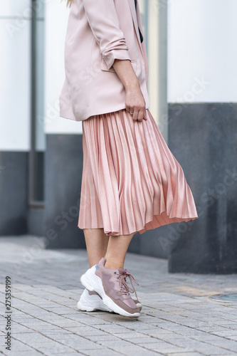 Stampa su Tela Model posing in a peach skirt, pleated, sneakers and jacket