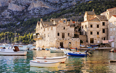 Sea village life in the town of Vis in Croatia with boats in the harbor.