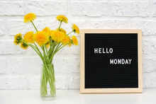 Hello Monday Words On Black Letter Board And Bouquet Of Yellow Dandelions Flowers On Table Against White Brick Wall. Concept Happy Monday. Template For Postcard