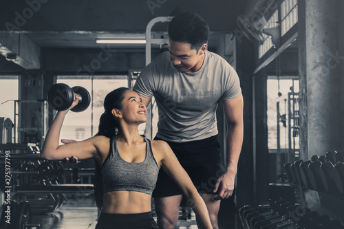 male trainer training female working out with dumbbells wieght lifting in gym
