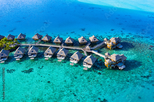 Obraz Travel vacation paradise aerial drone video with overwater bungalows in coral reef lagoon sea. Aerial video from Bora Bora, French Polynesia, Tahiti, South Pacific Ocean. - fototapety do salonu