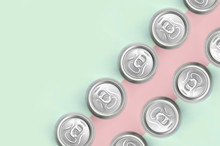 Many Metallic Beer Cans On Texture Background Of Fashion Pastel Turquoise And Pink Colors
