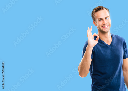 Photo of man showing okay hand sign gesture, over blue background, with copy spa Canvas Print