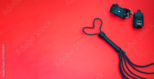 Accessories for bdsm on a red leather background Fototapeta