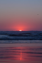 Scenic Deep Red Sunset Over Pacific Ocean, Oregon Coast. Red Sun Go Down Coloring Sly And Horizon In Purple And Red Colors Leaving A Thin Blurred Trace On A Wet Beach Sand. Waves Crushing On A Beach