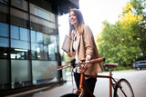 Fototapeta Panels - Young businesswoman standing on a city street with bicycle