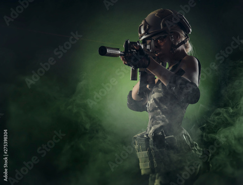 Foto the girl in military overalls airsoft posing with a gun in his hands on a dark b