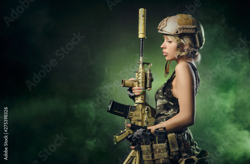 Fotografiet the girl in military overalls airsoft posing with a gun in his hands on a dark b