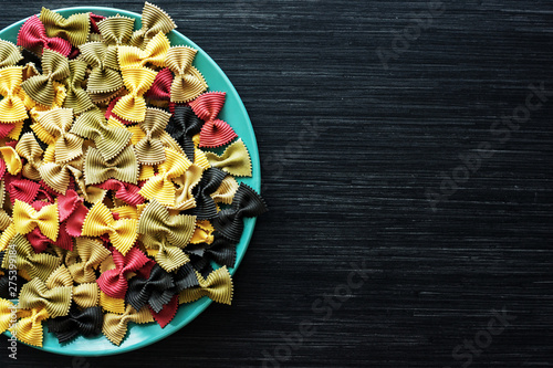 Multicolor italian raw pasta close-up in a ceramic plate on the dark wooden table Wallpaper Mural