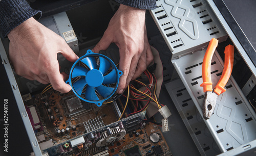 Man repairs cooling system of computer.