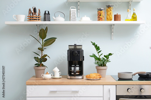 Modern coffee machine, cups and croissants on kitchen table Canvas Print
