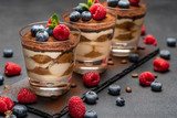 Classic tiramisu dessert with blueberries and raspberries in a glass on stone serving board on dark concrete background