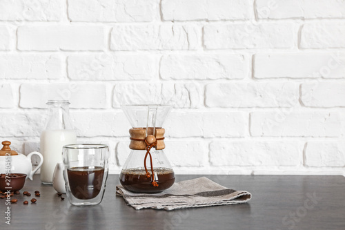 Fotografie, Obraz  Glass and chemex of hot coffee on table near brick wall