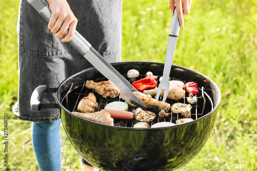 Spoed Foto op Canvas Grill / Barbecue Woman cooking tasty food on barbecue grill outdoors