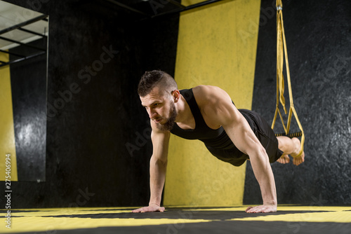 plakat Muscular man does exercises with fitness straps in the gym with black and yellow interior