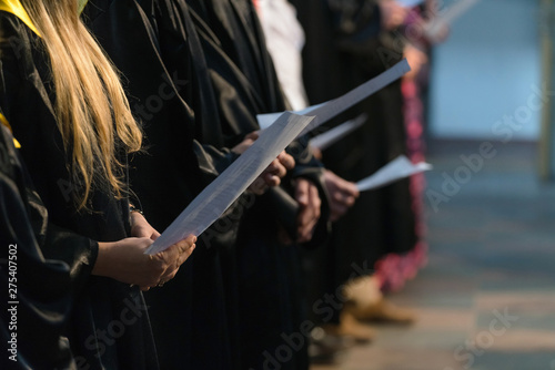 Photo Choir singers holding musical score and singing on student gradu