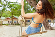 Beautiful young woman on a swing. Relax on vacation