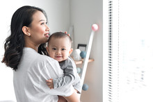 Beautiful Young Mom Is Playing With Her Cute Baby And Smiling While Standing Near The Window At Home