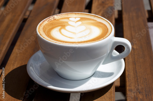 Fototapety, obrazy: Hot cappuccino with froth and pattern on wooden background, side view