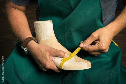 Obraz close up of orthopedic shoemaker measuring a wooden last - fototapety do salonu