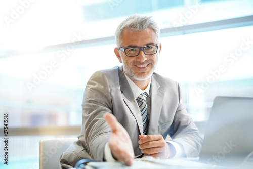 Fotomural Portrait of mature businessman sitting in office looking at camera