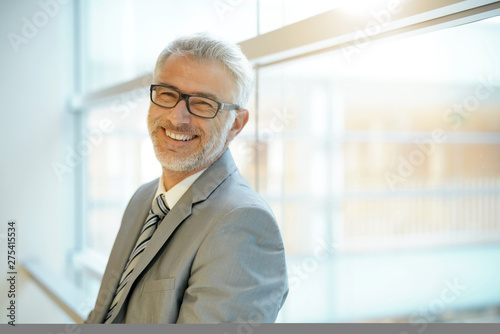 Photo Smiling mature businessman leaning on office window smiling at camera
