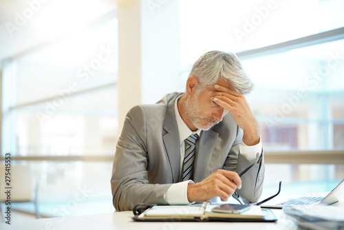 Exhausted businessman sitting at desk Fototapet