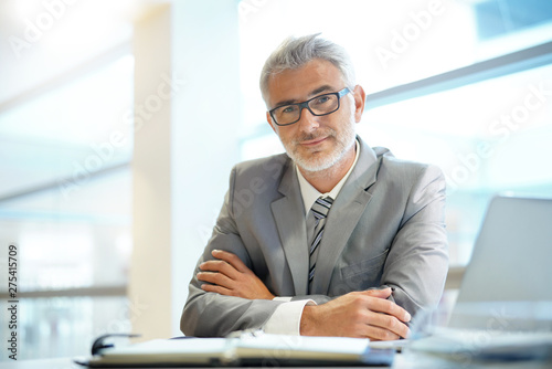 Obraz na płótnie Portrait of mature businessman sitting in office looking at camera