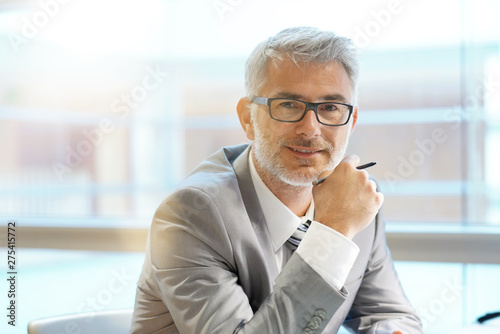 Photo Portrait of corporate businessman smiling at camera in office