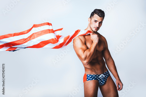 Obraz na plátně  Portrait of handsome young man with stylish haircut in swinwear posing with American flag over gray background