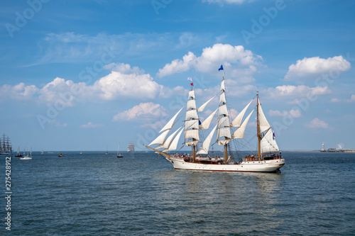 Antique tall ship, vessel leaving the harbor of The Hague, Scheveningen under a sunny and blue sky. © Ankor light