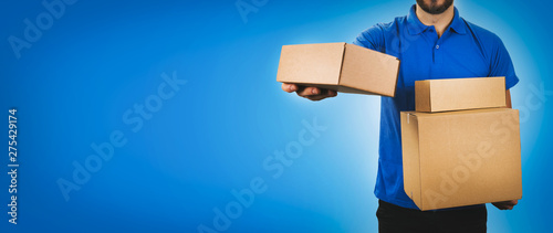Photo delivery service man holding cardboard boxes on blue background copy space