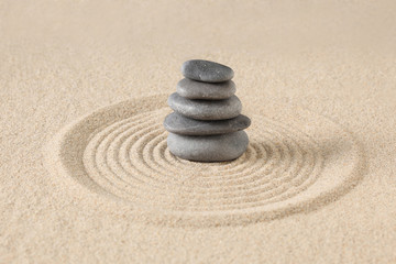 Fototapeta na wymiar zen stones piled on raked sand with copy space for your text