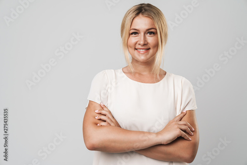 Obraz Cheerful happy beautiful young amazing blonde woman posing isolated over grey wall background dressed in basic white t-shirt. - fototapety do salonu