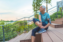 Senior Woman In Pain While Running In Park, Knee Injury. Senior Woman With An Expression Of Severe Pain In Her Leg. Athlete Woman Has Calf Crump, Pain In Leg During Running